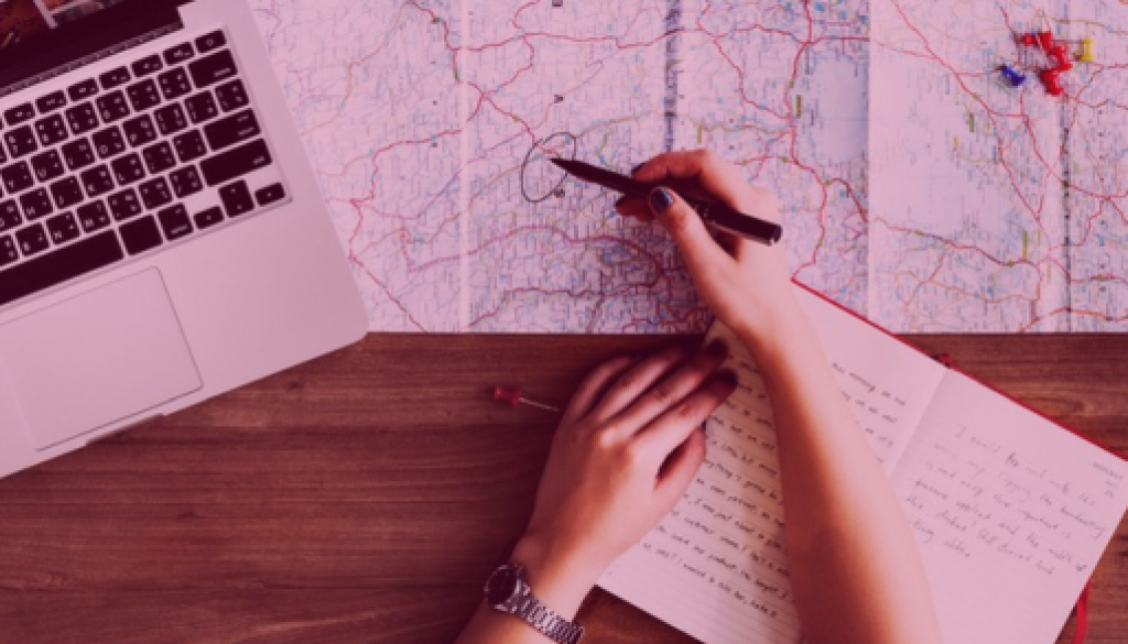 A person planning a road trip with a map, a journal and a computer